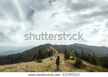 beautiful happy stylish traveling girl in the mountains on a background of a forest