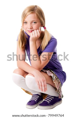 Beautiful happy teenage girl sitting squatted wearing knee socks, purple sporty shoes, shirt and colorful skirt, hand supporting her head, isolated.