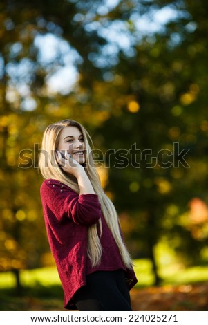 Beautiful happy teenage girl with phone in autumn park - stock photo