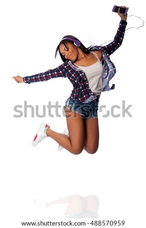 Beautiful happy teenager jumping dancing jamming listening to music, on white.