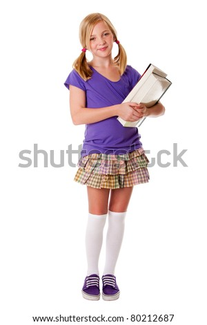 Beautiful happy teenager school girl carrying books, standing and smiling, isolated.
