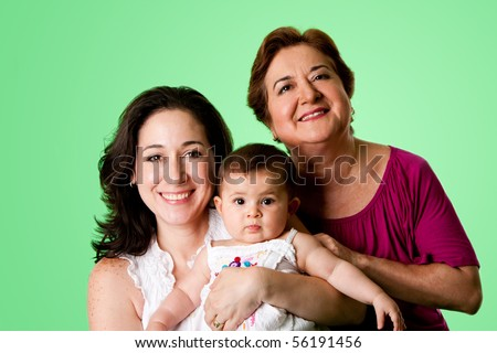 Beautiful happy three 3 generations of Caucasian Hispanic Latina women, grandmother, mother and baby girl, on green.
