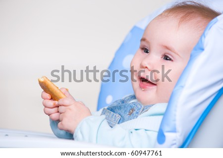 Beautiful happy toddler eating cookie sitting in chair