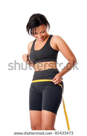 Beautiful happy toned woman weight conscious measuring her size shape around waist hips, celebrating her successful weightloss, dressed sporty in grey, isolated. - stock photo