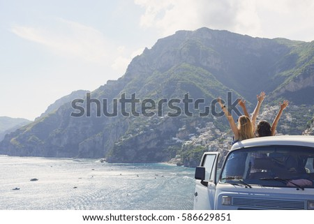 Beautiful happy tourist girl friends enjoying scenic view arms raised of Amalfi Coast on summer road trip adventure vacation in vintage van