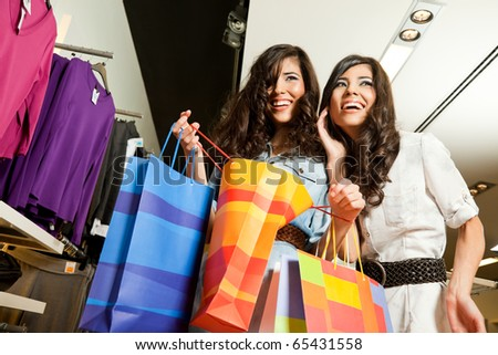 Beautiful happy twins holding present bags and smiling in fashion store - stock photo