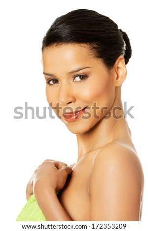 Beautiful happy woman after bath or spa, covered by green towel