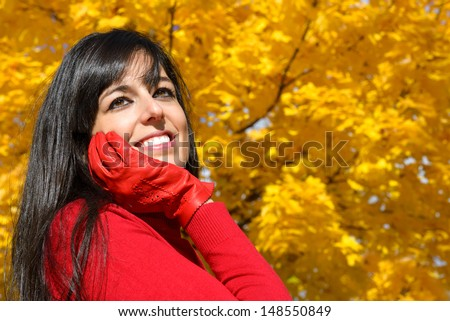 Beautiful happy woman autumn portrait. Dreamy cheerful woman on golden yellow autumnal foliage copy space background. - stock photo
