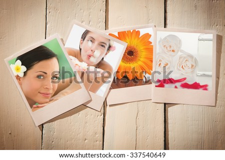 Beautiful happy woman blowing flower petals at spa center against pink petals with a glass flask and roses - stock photo