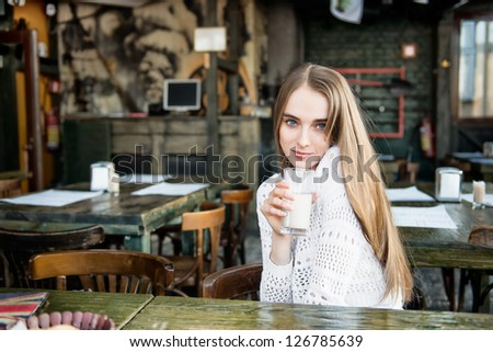 Beautiful happy woman drinking at the cafe - stock photo