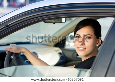 Beautiful happy woman driving her car - stock photo