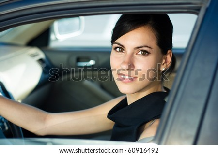 Beautiful happy woman driving her car