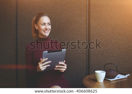 Beautiful happy woman enjoying good electronic book while is sitting at the table with cup of tea in modern coffee shop, smiling female thinking about something positive during work on digital tablet  - stock photo