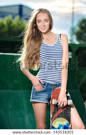 Beautiful happy woman holding her roller skates outdoors - stock photo