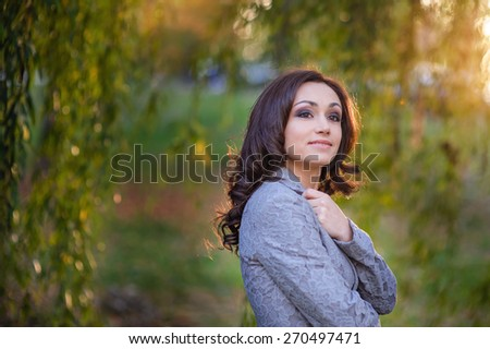 Beautiful happy woman in a gray suit for a walk in the summer park. - stock photo