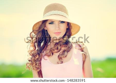 Beautiful happy woman in hat on summer meadow - stock photo