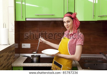 Beautiful happy woman in kitchen interior cooking - stock photo