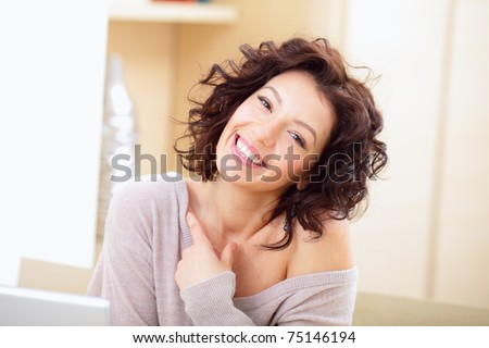 Beautiful happy woman indoors laughing - stock photo