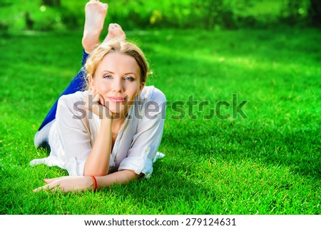 Beautiful happy woman lying on a grass outdoor and smilng.  - stock photo