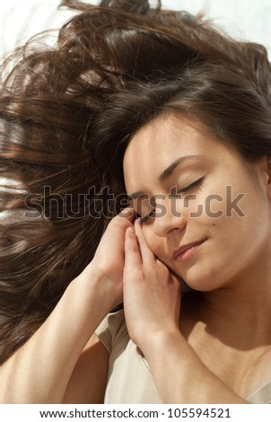 Beautiful happy woman lying on a pillow on a light background - stock photo