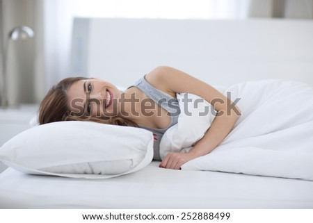 Beautiful happy woman lying on the bed at home