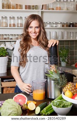 Beautiful happy woman making detox juice - stock photo