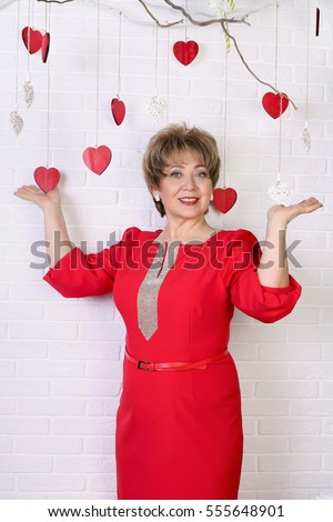 Beautiful happy woman of 50s in red dress holds in hands hearts