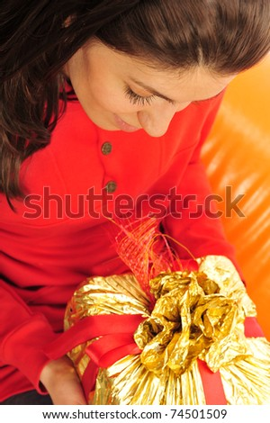 Beautiful happy woman on an orange sofa holding a gift in her arms