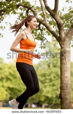 Beautiful happy woman running at the park - stock photo