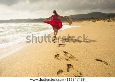 Beautiful happy woman running freely on the beach - stock photo