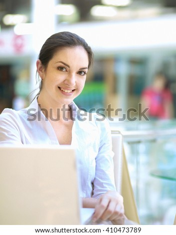 Beautiful happy woman sitting with laptop - stock photo