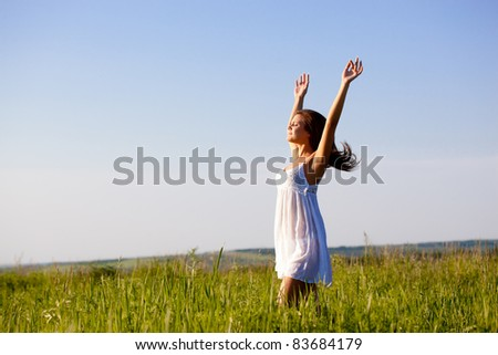 beautiful happy woman standing on green field over blue skies