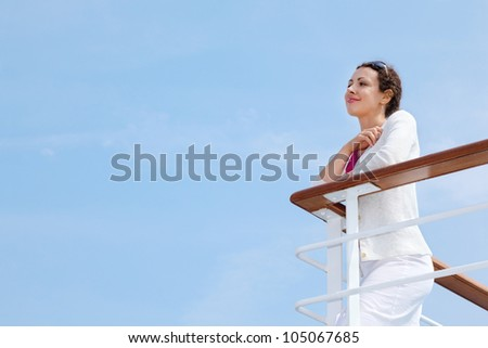 Beautiful happy woman stands on board of large ship and rests her hands on railing - stock photo