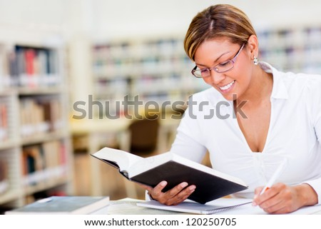Beautiful happy woman studying at the library - stock photo
