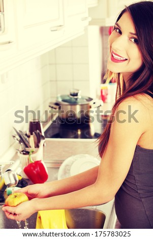 Beautiful happy woman washing tasty apple - stock photo