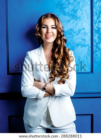 beautiful happy woman with amazing long hair wearing a white suit - stock photo