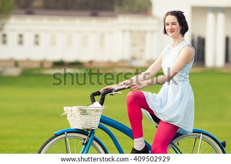 Beautiful happy woman with bicycle in the park relaxing in a beautiful spring day - stock photo