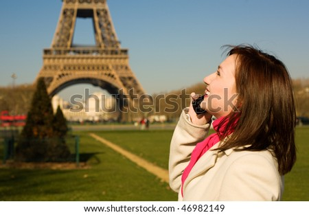 Beautiful happy woman with cell phone in Paris - stock photo