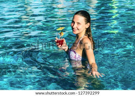 Beautiful happy woman with cocktail in pool in hot summer day - stock photo