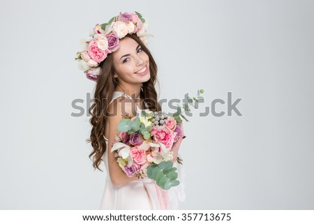 Beautiful happy young bride with long curly hair in rose wreath holding bouquet of flowers over white background - stock photo