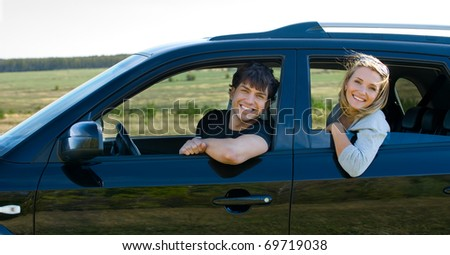 beautiful happy young couple driving the car - stock photo