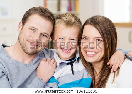 Beautiful happy young family posing together for a portrait with attractive young parents flanking a cute little boy with his front teeth missing - stock photo