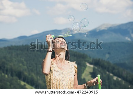 Beautiful happy young girl playing with soap bubbles