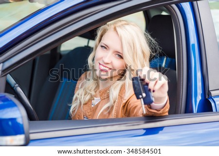 Beautiful happy young girl sitting in her car showing car key - stock photo