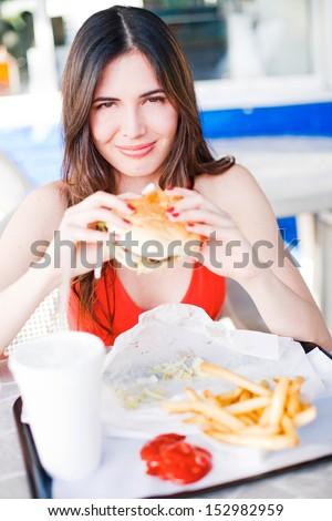 Beautiful happy young latin girl eating hamburger at fast food restaurant - stock photo