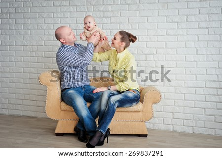 Beautiful happy young parents with baby smiling, family, lifestyle - stock photo