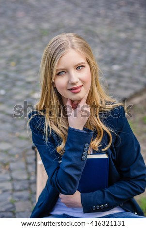 Beautiful, happy young student girl holding book sitting on the bench near the campus, university, school, education. Summer, spring green park pensive look - stock photo