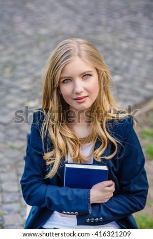 Beautiful, happy young student girl holding book sitting on the bench near the campus, university, school, education. Summer, spring green park - stock photo