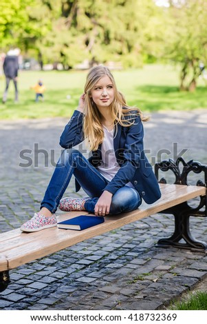 Beautiful, happy young student girl holding book sitting on the bench under the tree near the campus, university, school, education. Summer, spring green park - stock photo