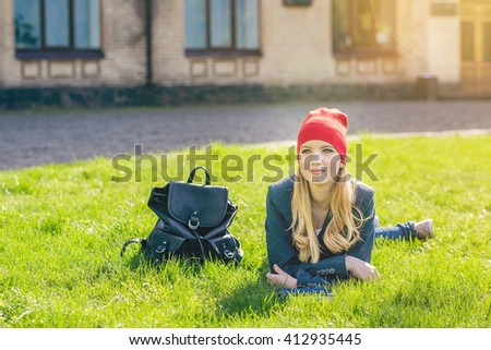 Beautiful, happy young student girl in red hat holding book lying on green grass under the tree near the campus, university, school, education. Summer, spring green park, bright sunshine - stock photo
